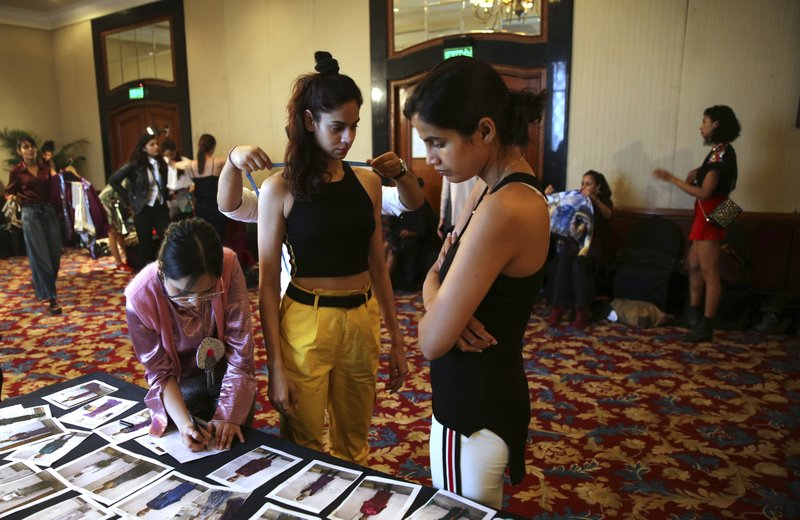 In this Monday, March 11, 2019, photo, a tailor takes measurements of a model as a woman scans photographs during a fitting session ahead of the Lotus Makeup India Fashion Week, in New Delhi, India. (AP Photo/Manish Swarup)