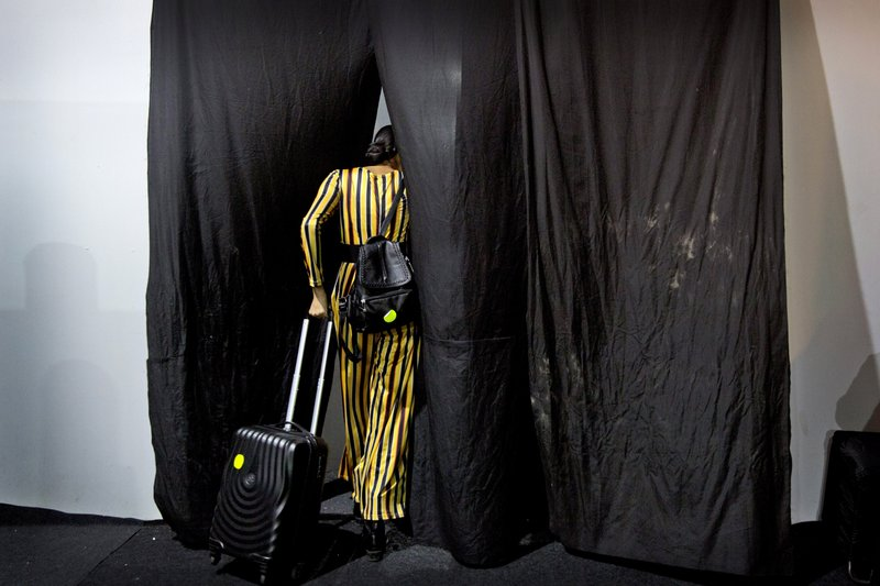 In this Thursday, March 14, 2019, photo, a model leaves the backstage after showcasing creations of Indian designers for the Lotus Makeup India Fashion Week, in New Delhi, India. (AP Photo/Manish Swarup)