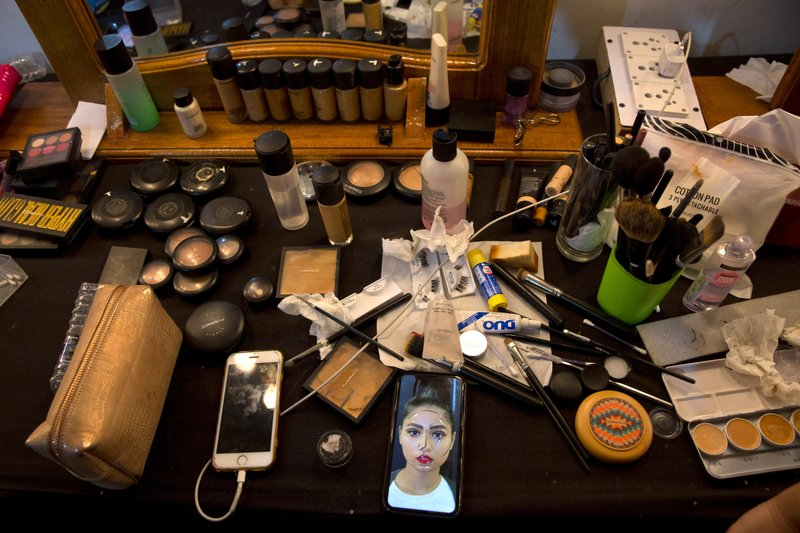 In this Thursday, March 14, 2019, photo, a photograph of an Indian model is seen on the mobile phone of a makeup artist at the main makeup room for models during Lotus Makeup India Fashion Week, in New Delhi, India. (AP Photo/Manish Swarup)