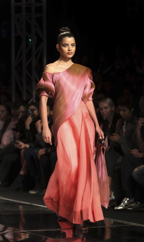 In this Saturday, March 16, 2019, photo, a model displays a creation of one of the top Indian designers celebrating the Sari, a traditional Indian attire, during the Grand finale of the Lotus make up India Fashion Week in New Delhi, India. (AP Photo/Manish Swarup)