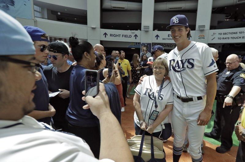 Tampa Bay Rays relief pitcher Tyler Glasnow poses for photos with fans as the gates to the stadium open for an opening day baseball game between the Rays and the Houston Astros, Thursday, March 28, 2019, in St. (AP Photo/Chris O'Meara)