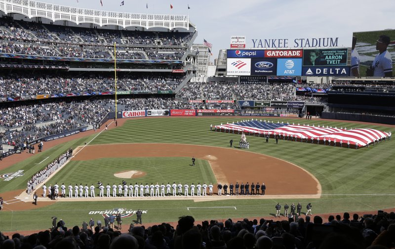 A large flag is unfurled during the national anthem before an opening day baseball game between the New York Yankees and the Baltimore Orioles at Yankee Stadium, Thursday, March 28, 2019, in New York. (AP Photo/Seth Wenig)