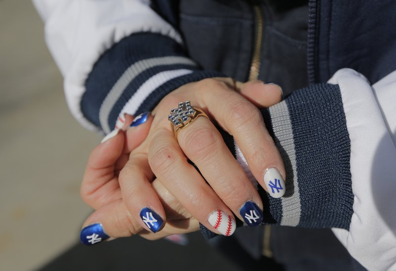 Dana Fontanez keeps her hands warm before the start of an opening day baseball game between the New York Yankees and the Baltimore Orioles at Yankee Stadium, Thursday, March 28, 2019, in New York. (AP Photo/Seth Wenig)