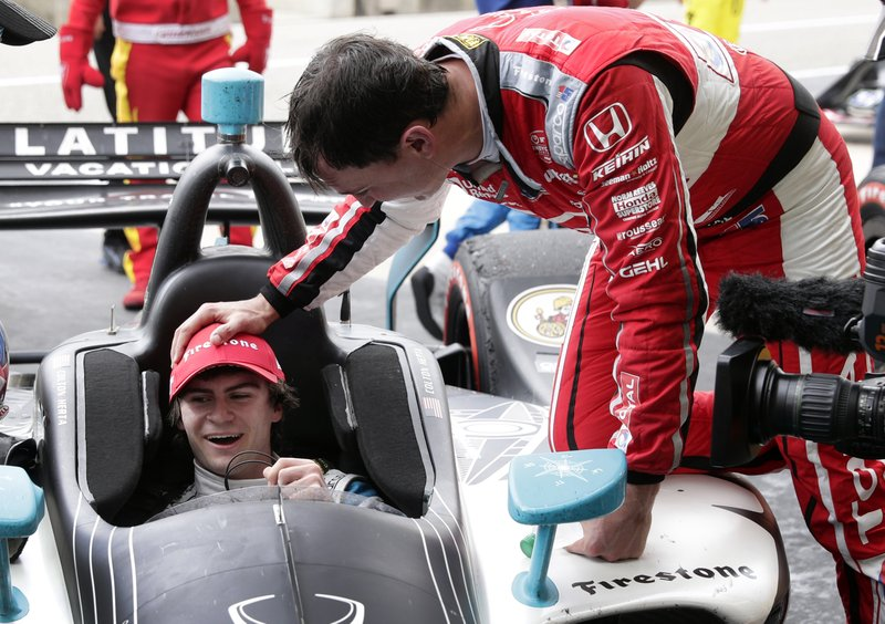Colton Herta sits in his car on pit road as receives congratulations from Graham Rahal for winning the IndyCar Classic auto race Sunday, March 24, 2019, in Austin, Texas. (AP Photo/Eric Gay)