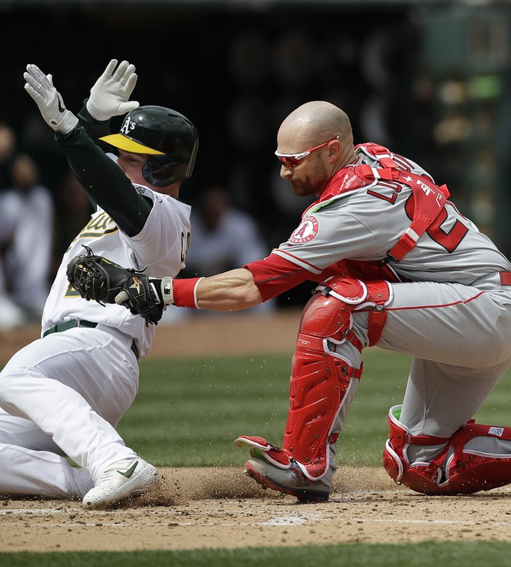 Oakland Athletics' Matt Chapman, left, is tagged out by Los Angeles Angels catcher Jonathan Lucroy in the third inning of a baseball game Thursday, March 28, 2019, in Oakland, Calif. (AP Photo/Ben Margot)