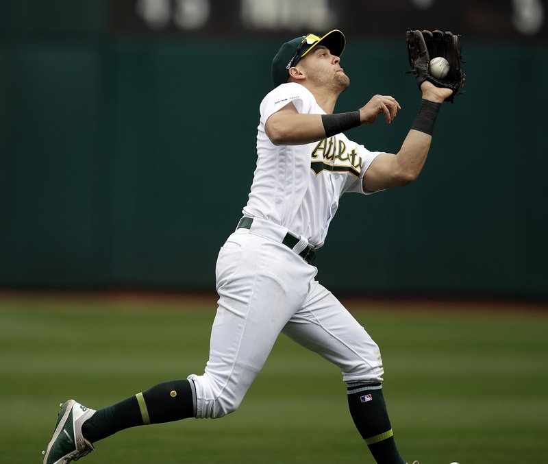 Oakland Athletics' Chad Pinder catches a ball hit by Los Angeles Angels' Mike Trout in the sixth inning of a baseball game Thursday, March 28, 2019, in Oakland, Calif. (AP Photo/Ben Margot)