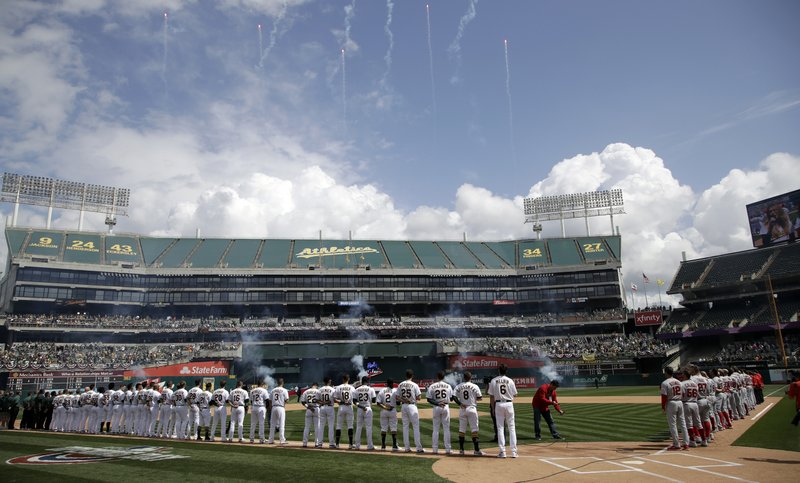 The Oakland Athletics and Los Angeles Angels watch fireworks during the national anthem prior to a baseball game Thursday, March 28, 2019, in Oakland, Calif. (AP Photo/Ben Margot)