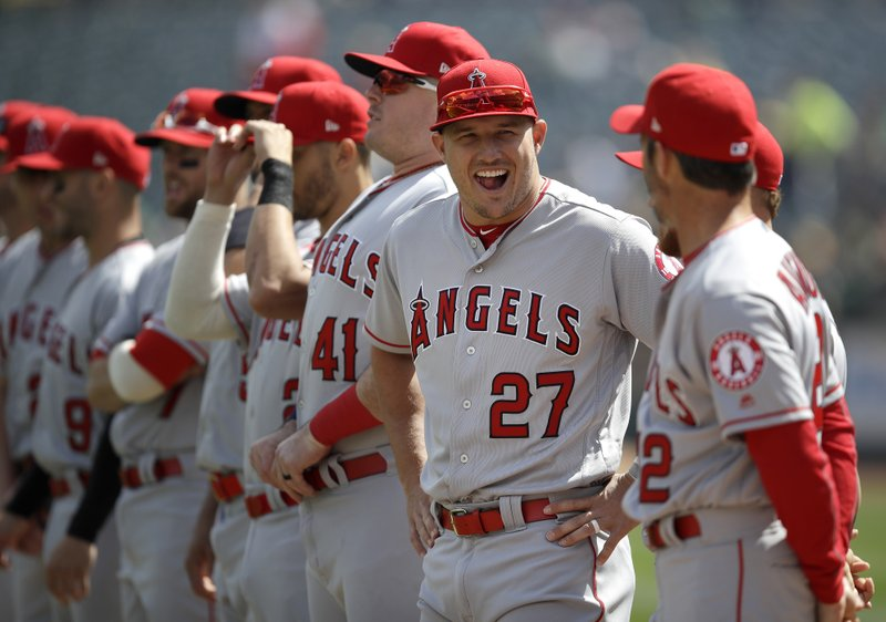 Los Angeles Angels' Mike Trout (27) laughs with teammates prior to an opening day baseball game against the Oakland Athletics, Thursday, March 28, 2019, in Oakland, Calif. (AP Photo/Ben Margot)