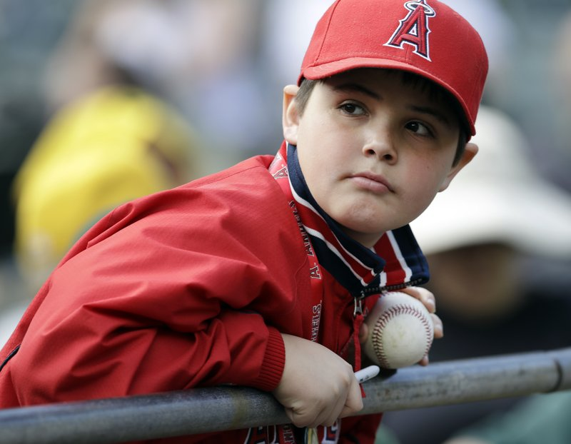 A young Los Angeles Angels fan looks for a player to autograph his baseball prior to an opening day baseball game against the Oakland Athletics, Thursday, March 28, 2019, in Oakland, Calif. (AP Photo/Ben Margot)