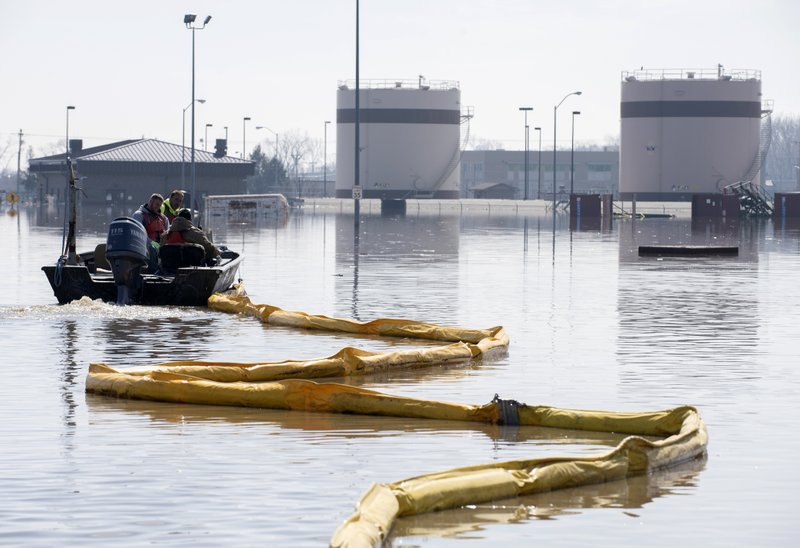 FILE - In this March 18, 2019 file photo released by the U.S. Air Force, environmental restoration employees deploy a containment boom from a boat on Offutt Air Force Base in Nebraska, as a precautionary measure for possible fuel leaks in the flooded area. (Delanie Stafford/U.S. Air Force via AP, File)