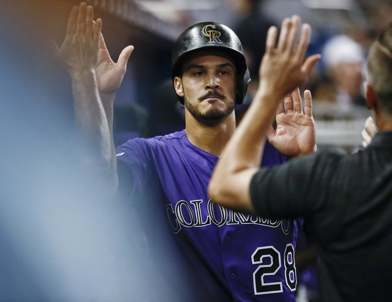 Colorado Rockies' Nolan Arenado (28) is congratulated after scoring during fourth inning of the team's baseball game against the Miami Marlins on Thursday, March 28, 2019, in Miami. (AP Photo/Brynn Anderson)