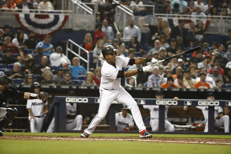 Miami Marlins' Starlin Castro (13) hits a single in the fourth inning during a baseball game against the Colorado Rockies, Thursday, March 28, 2019, in Miami. (AP Photo/Brynn Anderson)