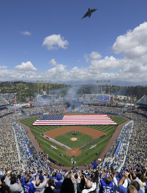 Fans stand for the national anthem as a C-17 Globemaster flies over before an opening day baseball game between the Los Angeles Dodgers and the Arizona Diamondbacks Thursday, March 28, 2019, in Los Angeles. (AP Photo/Mark J. Terrill)