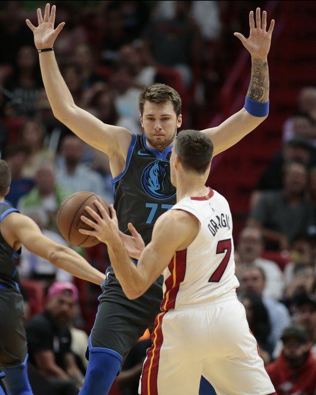 Dallas Mavericks forward Luka Doncic (77) defends against Miami Heat guard Goran Dragic (7) during the first half of an NBA basketball game, Thursday, March 28, 2019, in Miami. (AP Photo/Joel Auerbach)