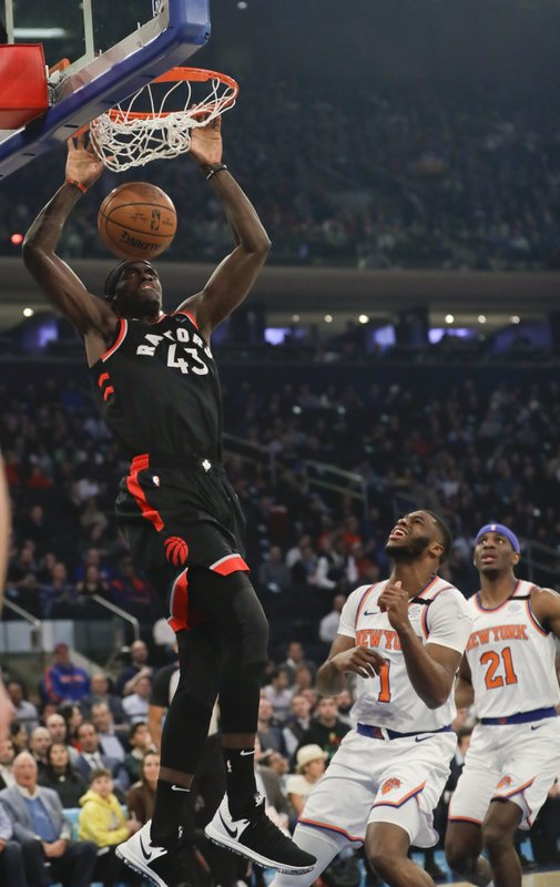 New York Knicks' Emmanuel Mudiay (1) and Damyean Dotson (21) watch as Toronto Raptors' Pascal Siakam (43) dunks during the first half of an NBA basketball game Thursday, March 28, 2019, in New York. (AP Photo/Frank Franklin II)