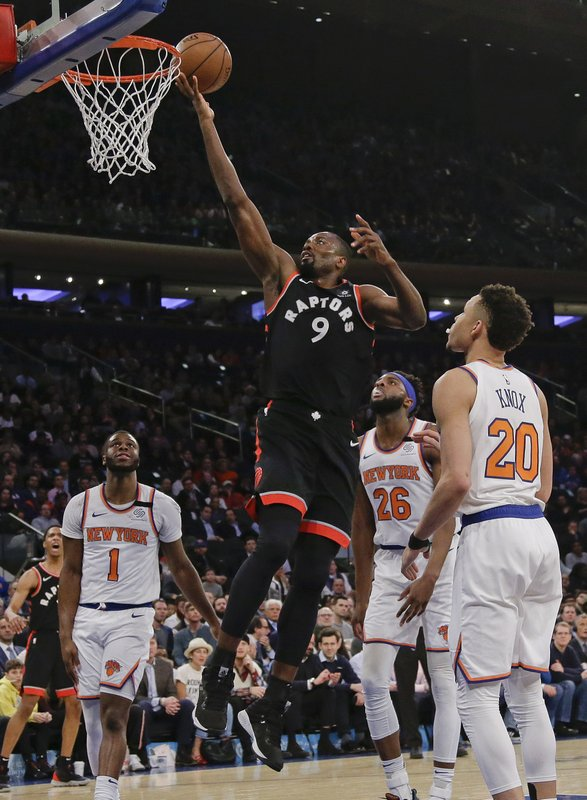 Toronto Raptors' Serge Ibaka (9) drives past New York Knicks' Kevin Knox (20) during the first half of an NBA basketball game Thursday, March 28, 2019, in New York. (AP Photo/Frank Franklin II)