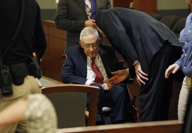 Former U.S. Sen. Harry Reid, center, sits in a wheelchair in court, Thursday, March 28, 2019, in Las Vegas. (AP Photo/John Locher)