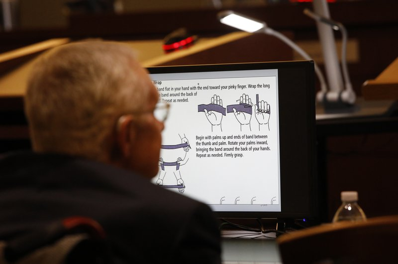 Former U.S. Sen. Harry Reid sits in front of a monitor showing instructions for an exercise band in court Tuesday, March 26, 2019, in Las Vegas. (AP Photo/John Locher)