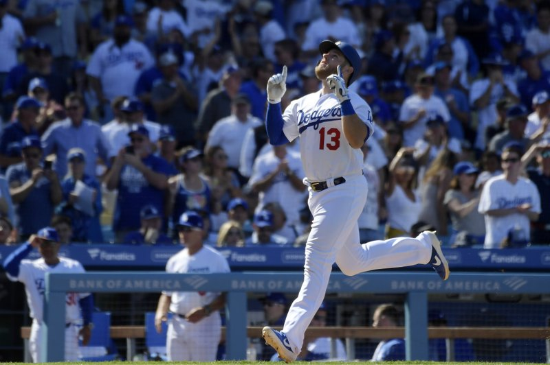 Los Angeles Dodgers' Max Muncy celebrates as he heads home after hitting a solo home run during the seventh inning of a baseball game against the Arizona Diamondbacks, Thursday, March 28, 2019, in Los Angeles. (AP Photo/Mark J. Terrill)