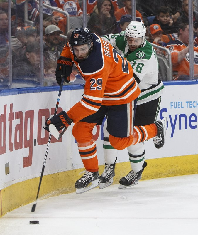 Dallas Stars' Jason Dickinson (16) and Edmonton Oilers' Leon Draisaitl (29) battle for the puck during first-period NHL hockey game action in Edmonton, Alberta, Thursday March 28, 2019. (Jason Franson/The Canadian Press via AP)