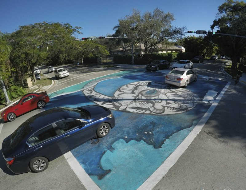 In this, Wednesday, Feb. 6, 2019 photo, a large number six, stating that the area is six feet above sea level, is painted in an intersection in Pinecrest, Fla. (AP Photo/Wilfredo Lee)