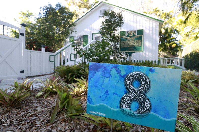 In this Wednesday, Feb. 6, 2019 photo, a yard sign stating that the area is eight feet above sea level is shown in front of artist Xavier Cortada's studio in Pinecrest, Fla. (AP Photo/Wilfredo Lee)
