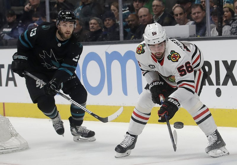 Chicago Blackhawks defenseman Erik Gustafsson (56) watches the puck in front of San Jose Sharks right wing Barclay Goodrow during the first period of an NHL hockey game in San Jose, Calif. (AP Photo/Jeff Chiu)