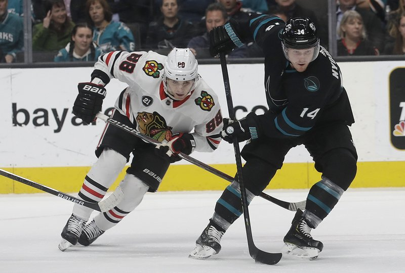 San Jose Sharks center Gustav Nyquist (14) skates in front of Chicago Blackhawks right wing Patrick Kane (88) during the first period of an NHL hockey game in San Jose, Calif. (AP Photo/Jeff Chiu)