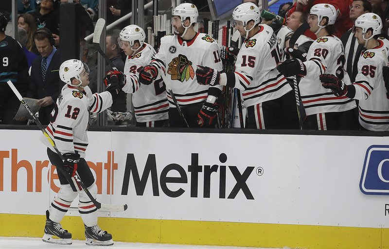 Chicago Blackhawks left wing Alex DeBrincat (12) is congratulated by teammates after scoring a goal against the San Jose Sharks during the first period of an NHL hockey game in San Jose, Calif. (AP Photo/Jeff Chiu)