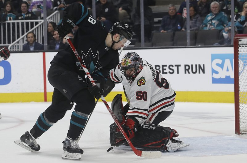 Chicago Blackhawks goaltender Corey Crawford (50) defends against a shot attempt by San Jose Sharks center Tomas Hertl during the first period of an NHL hockey game in San Jose, Calif. (AP Photo/Jeff Chiu)