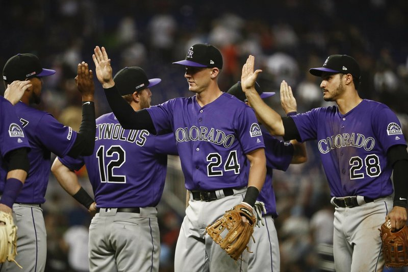 Colorado Rockies' Ryan McMahon (24), Nolan Arenado (28), and Mark Reynolds (12) celebrate the team's 6-3 win against the Miami Marlins in a baseball game Thursday, March 28, 2019, in Miami. (AP Photo/Brynn Anderson)