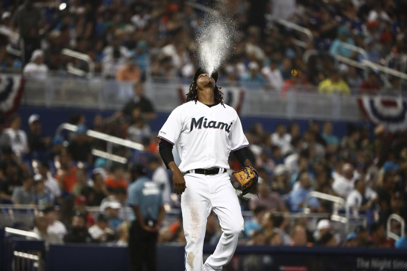 Miami Marlins starting pitcher Jose Urena does a ritual on his way to the mound during the second inning of the team's baseball game against the Colorado Rockies on Thursday, March 28, 2019, in Miami. (AP Photo/Brynn Anderson)