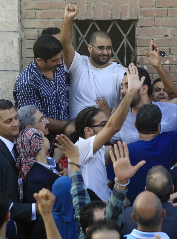FILE - In this Aug. 28, 2014 file photo, surrounded by plainclothes policemen, Egyptian prominent blogger Alaa Abdel-Fattah waves to the crowd after attending the funeral of his father, Ahmed Seif, in Cairo, Egypt. (AP Photo/Hassan Ammar, File)