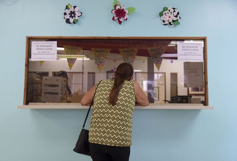 A Puerto Rican citizen applies for an assistance program at the Department of Family Affairs, in Bayamon, Puerto Rico, Friday, March 29, 2019. (AP Photo/Carlos Giusti)
