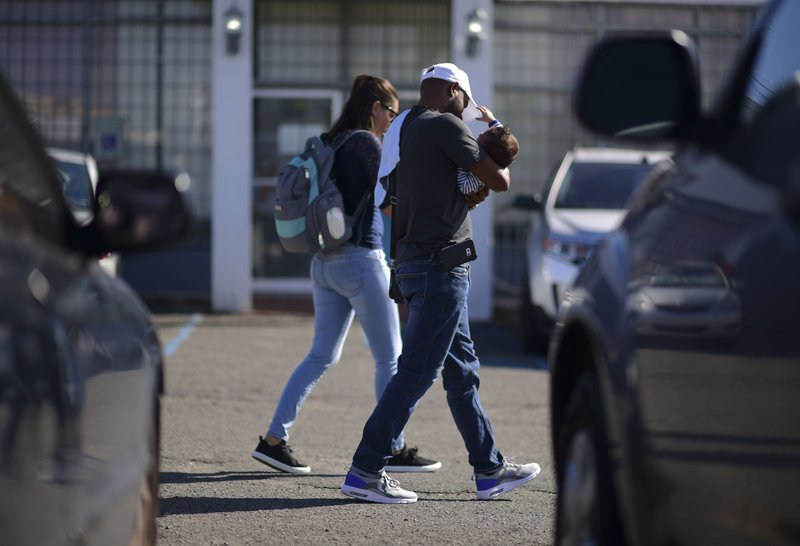 A family arrives at the Department of Family Affairs where many come to apply for the nutritional assistance program, in Bayamon, Puerto Rico, Friday, March 29, 2019. (AP Photo/Carlos Giusti)