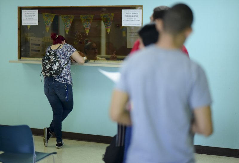 A woman fills out a form at a receiving window as others wait their turn at the Department of Family Affairs, in Bayamon, Puerto Rico, Friday, March 29, 2019. (AP Photo/Carlos Giusti)
