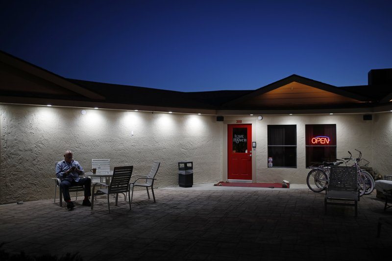 File - In this April 27, 2018, file photo, owner Dennis Hof sits in front of the Love Ranch brothel in Crystal, Nev. (AP Photo/John Locher, File)