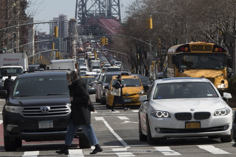 In this March 28, 2019 photo, pedestrians cross Delancey Street as traffic is seen making its way into Manhattan from Brooklyn over the Williamsburg Bridge, in New York. (AP Photo/Mary Altaffer)