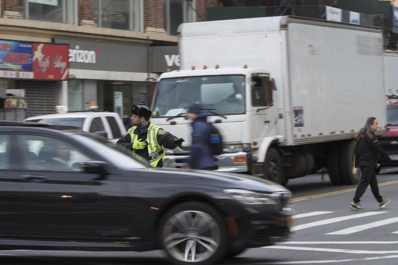 In this March 28, 2019 photo,  a police officer directs rush hour traffic on Canal Street in New York. (AP Photo/Mary Altaffer)