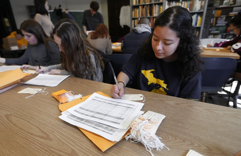 Ximena Mancilla, who came to the U.S. from Mexico in 2011 and a freshman at the University of Michigan, fills out a toe tag in Ann Arbor, Mich. (AP Photo/Paul Sancya)