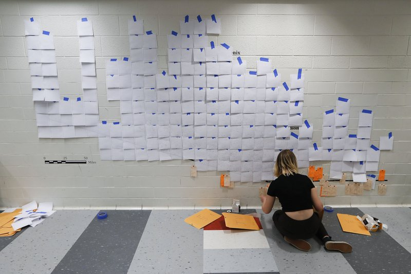 Lucy Cahill works on putting toe tags on a wall in Ann Arbor, Mich., Wednesday, March 27, 2019. The giant map of Arizona in the hallway of a University of Michigan classroom building steadily fills with orange and tan tags. (AP Photo/Paul Sancya)