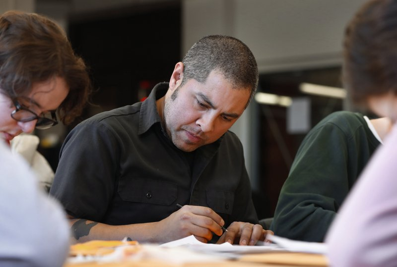 Jason De Leon, a University of Michigan anthropology professor, fills out toe tags in Ann Arbor, Mich. (AP Photo/Paul Sancya)
