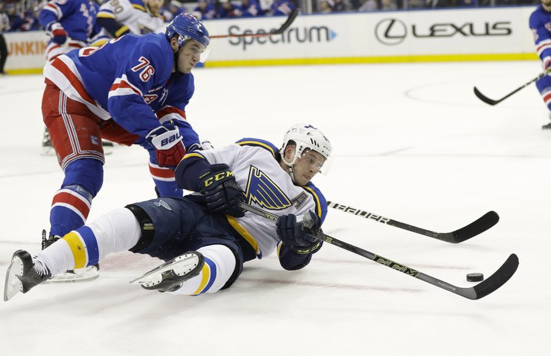 New York Rangers' Brady Skjei, left, fights for control of the puck with St. Louis Blues' Vladimir Tarasenko during the first period of an NHL hockey game Friday, March 29, 2019, in New York. (AP Photo/Frank Franklin II)