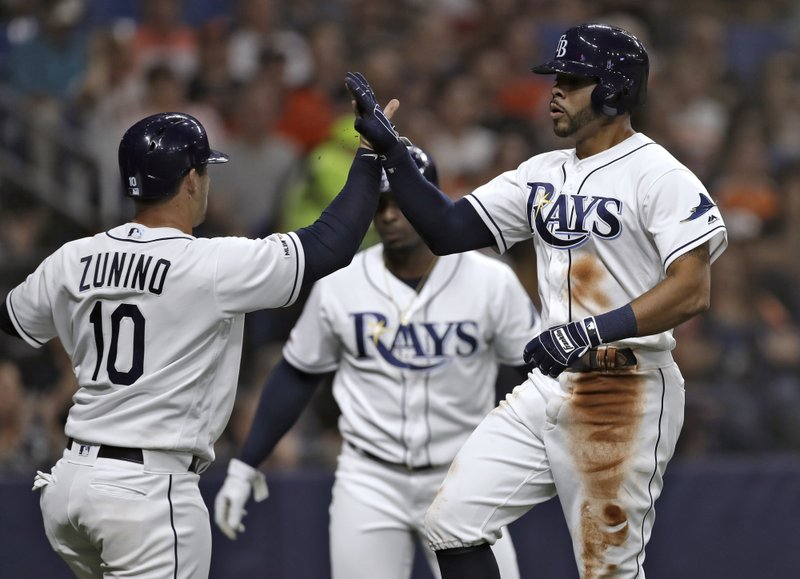 Tampa Bay Rays' Tommy Pham, right, celebrates with Mike Zunino after the pair scored on a two-run single by Ji-Man Choi off Houston Astros starting pitcher Gerrit Cole during the third inning of a baseball game Friday, March 29, 2019, in St. (AP Photo/Chris O'Meara)