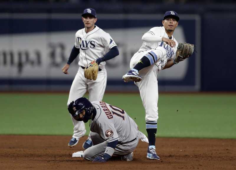 Tampa Bay Rays shortstop Willy Adames, right, and second baseman Daniel Robertson, left, team up to turn a double play on Houston Astros' Yuli Gurriel (10) and Josh Reddick during the sixth inning of a baseball game Friday, March 29, 2019, in St. (AP Photo/Chris O'Meara)