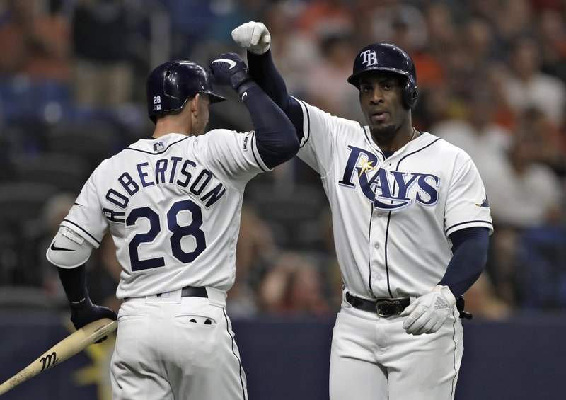 Tampa Bay Rays' Yandy Diaz celebrates his home run off Houston Astros starting pitcher Gerrit Cole with Daniel Robertson (28) during the sixth inning of a baseball game Friday, March 29, 2019, in St. (AP Photo/Chris O'Meara)