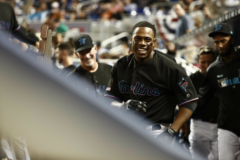 Miami Marlins' Curtis Granderson celebrates in the dugout after hitting a solo home run during the fourth inning of a baseball game against the Colorado Rockies on Friday, March 29, 2019, in Miami. (AP Photo/Brynn Anderson)