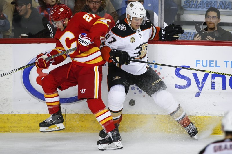 Anaheim Ducks' Hampus Lindholm, right, and Calgary Flames' Austin Czarnik collide during the third period of an NHL hockey game Friday, March 29, 2019, in Calgary, Alberta. (Jeff McIntosh/The Canadian Press via AP)