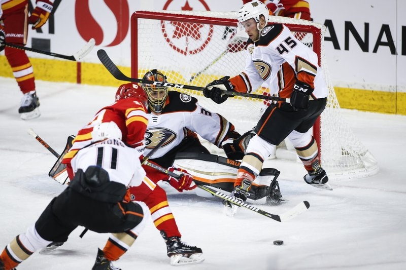 Anaheim Ducks' Andy Welinski, right, and goalie Ryan Miller, center, block the net on Calgary Flames' Johnny Gaudreau during the second period of an NHL hockey game Friday, March 29, 2019, in Calgary, Alberta. (Jeff McIntosh/The Canadian Press via AP)