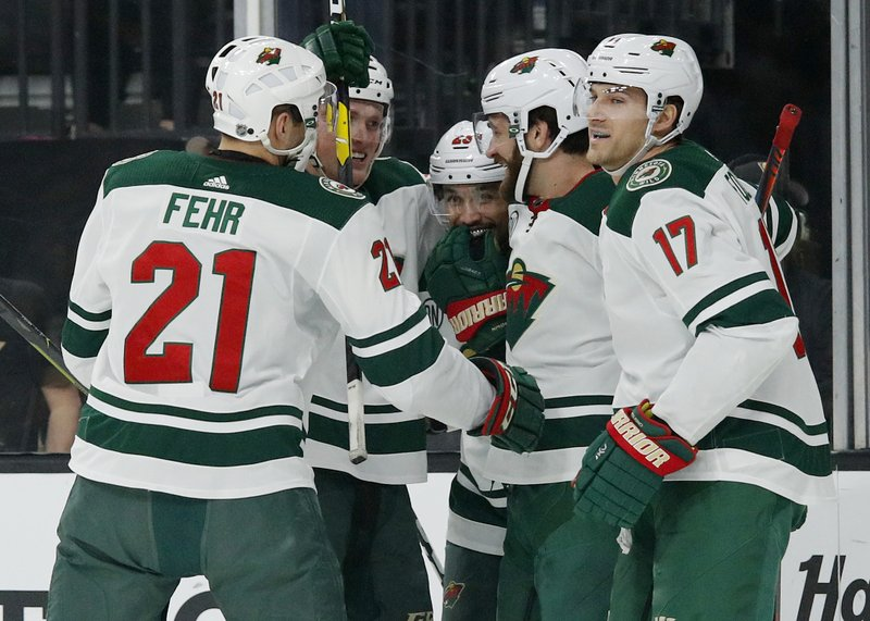 Minnesota Wild players celebrate after defenseman Greg Pateryn, second from right, scored against the Vegas Golden Knights during the first period of an NHL hockey game Friday, March 29, 2019, in Las Vegas. (AP Photo/John Locher)